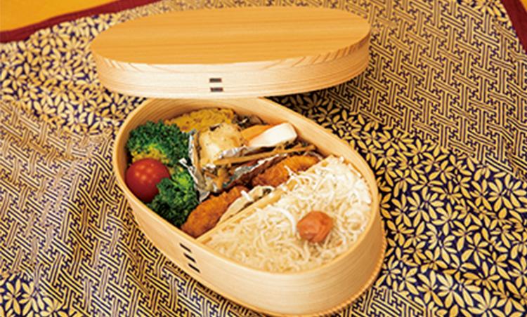 <p>お気に入りの秋田曲げわっぱの弁当箱で持参する奥様手作りの弁当は、傾かないように一番下に入れる。健康を考えた野菜豊富なメニューで、好物の卵焼きは大定番だ。</p>