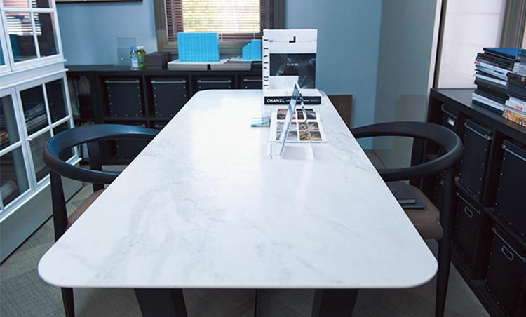 <p>傷付きにくい1枚タイル天板のテーブル。明るい場所に置かれ、資材サンプル等を検討するのにも活用。</p>