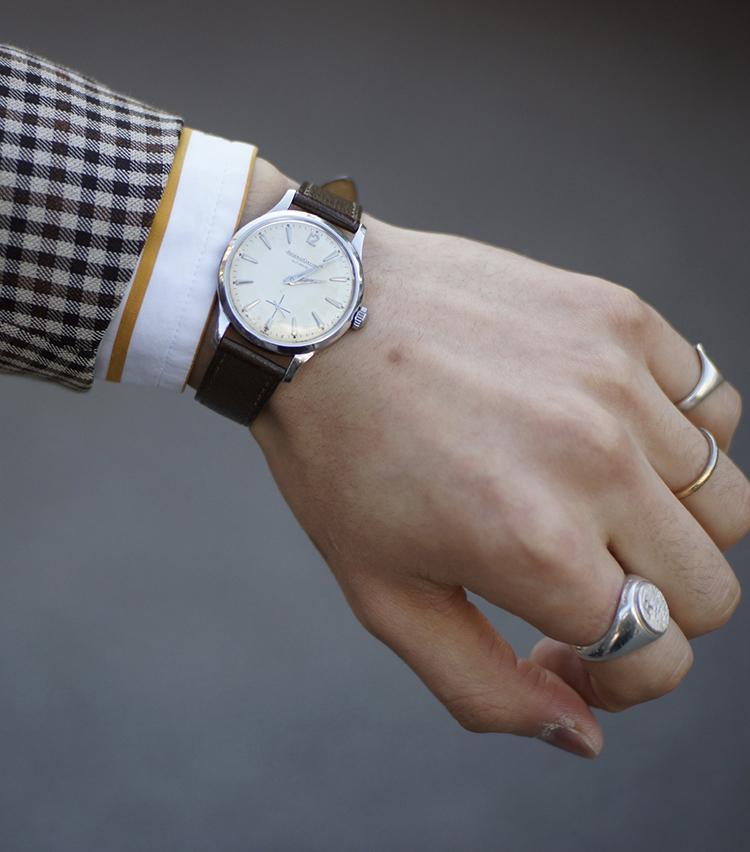 <p><strong>ビームス ハウス 丸の内 齋藤龍治さんの愛用時計<br /> ジャガー・ルクルト/1960年代アンティーク(モデル名不明)</strong><br /> 「6年くらい前の誕生日にお客様に頂いた物。バックヤード作業中にぶつけてリューズを飛ばしてしまって(そのまま紛失)修理代が高くついたが、余計に愛着が湧いた。ベルトは某H社出身の職人が手がけるLICの物。シンプルで何でもないんだけど、品があるのがお気に入り。アクセサリーでごちゃごちゃしている人が苦手なので、リングだけにしています」<br /> <a href=
