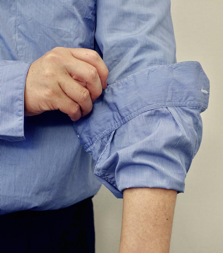 <p><strong>【その3】きれいめシャツで実践したい「ドレスまくり」</strong><br /> 1.まず、袖を大きくまくりあげる。だいたいカフ2〜3個ぶんの長さが目安だ。</p>