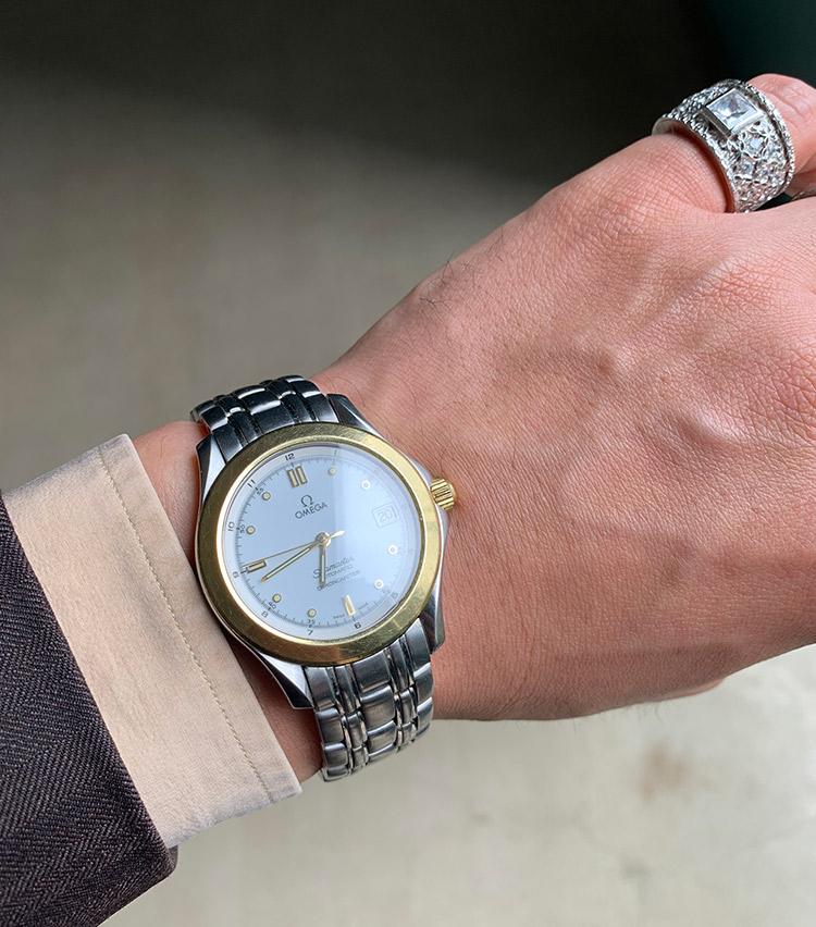 <p><strong>バーニーズ ニューヨーク PR 新井慶太さんの愛用時計<br />オメガ/シーマスター</strong><br /> 「歴史が深く、伝統を重んじるヨーロッパでは装飾品は親から子へ、子から孫へと受け継がれていくものとして知られています。僕の中で時計はまさにその家族の系譜を表すもので、これは義父より譲り受けた一本です。18Kイエローゴールドとステンレススチールとのコンビネーションがアクセサリーやバッグの金具との相性もよく、愛用しています。今後も僕の人生に於いて欠かすことのできない唯一無二の時計です」</p> <p><a class=