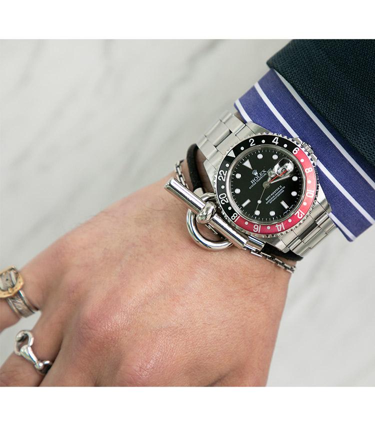 <p><strong>ストラスブルゴ事業部 ブランドマネージャー 兼 販売支援部 部長 門石貴幸さんの愛用時計(1)<br /> ロレックス/GMTマスターⅡ 16710</strong><br /> 「20代前半に2本目のROLEXとして購入したGMT MASTERⅡ。 投入時は青赤ベゼルと迷った末、黒赤ベゼルを選択。40㎜のケースサイズのバランスも良く、幅広いジャンルのファッションに応用できるのも魅力の一つ。スポーティーな見た目ながら、エレガントなスタイルにも柔軟に対応できるマスターピースです」</p>