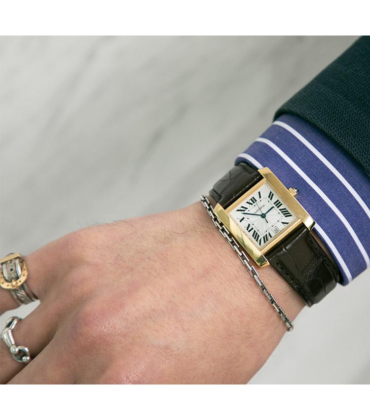 <p><strong>ストラスブルゴ事業部 ブランドマネージャー 兼 販売支援部 部長 門石貴幸さんの愛用時計(2)<br /> カルティエ/タンク フランセーズ </strong><br /> 「ドレススタイルに合う時計を探した末に、選んだ1本。カルティエのタンクシリーズの中でも、自動巻きのフランセーズを選んだのは希少なだけでなく、メンズサイズにしては少し小ぶりなフェイスと18Kケースに惹かれたから。クラシックなスタイルにも合わせやすい、アリゲーターストラップのコンビもポイント」</p> <p><a class=