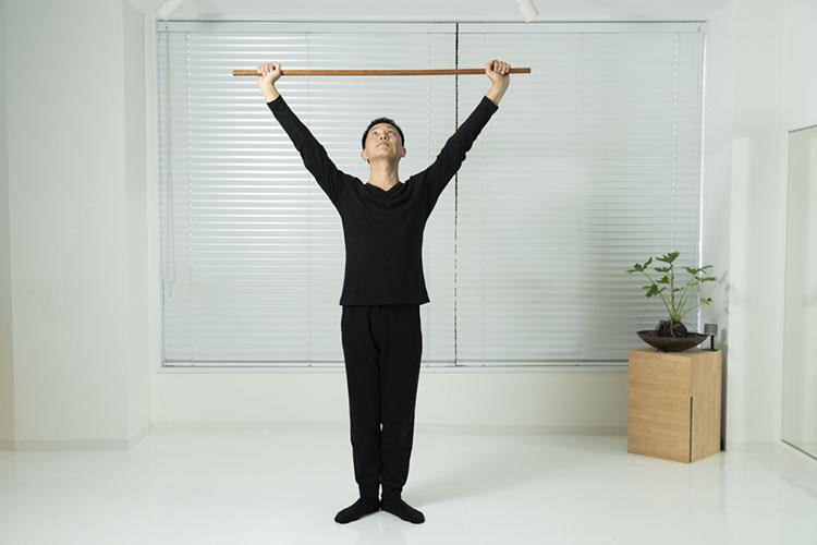 <p>両手を伸ばして棒を頭の上へ上げ、かかとも上げて身体を伸ばす。このとき、視線を棒に向けるようにする。</p>
