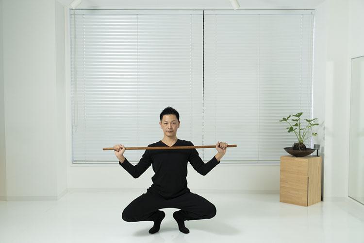 <p>再び、鎖骨の高さに棒を戻し、膝を曲げて、蹲踞(そんきょ=腰を落とし、膝を曲げ、かかとを上げた姿勢。相撲や剣道の試合のときに、相手と対峙する際の姿勢)する。</p>