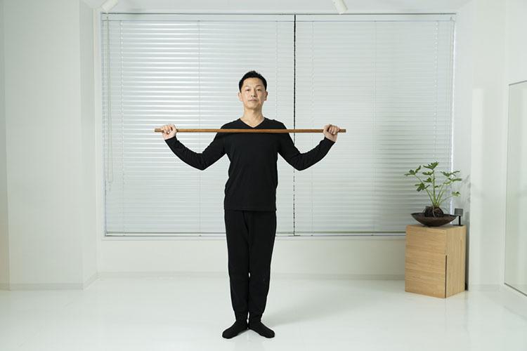 <p>鎖骨の高さで棒を持ち、まっすぐに立つ。足先は八の字くらいに開いておく。</p>