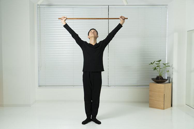 <p>両手を伸ばして棒を頭の上へ上げ、身体を伸ばす。このとき、視線を棒に向けるようにする。</p>