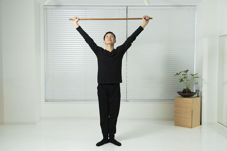 <p>両手を上に上げながら、床を押すようにして腰を上げ、右脚を左脚にそろえる。</p>