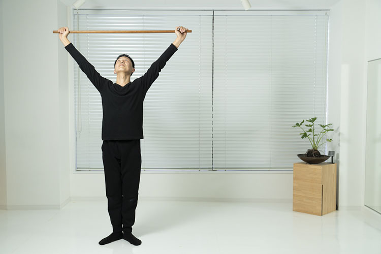 <p>両手を上に上げながら、床を押すようにして腰を上げ、左脚を右脚にそろえ、スタートの位置に戻る。これを左右同様に12回ずつで1セットを繰り返す。スクワット2は、蹲踞をするときに、棒を首の後ろに持ってくる(動画参照)。その他はスクワット1と同様。</p>