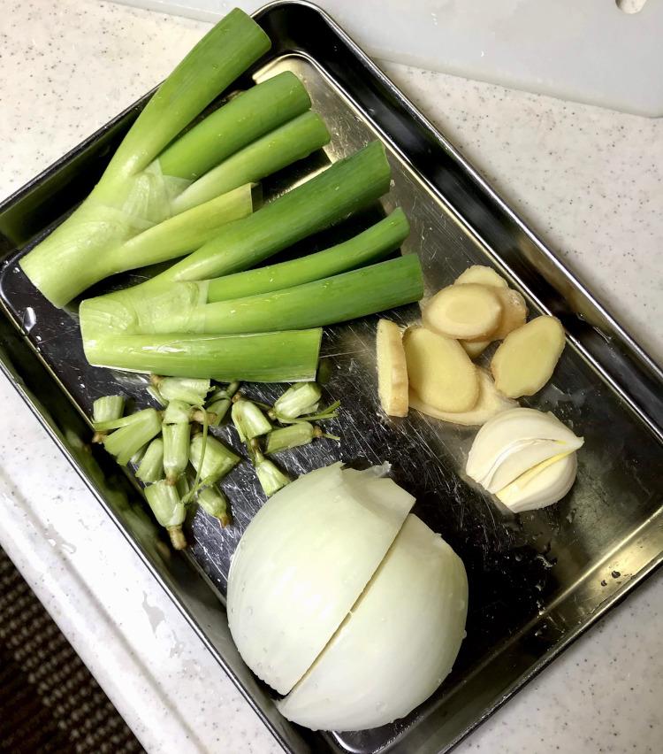 <p>8.野菜の下ごしらえをする。ネギの青い部分はそのまま、玉ねぎは半分にカット。生姜、ニンニクは薄切りにする。</p>