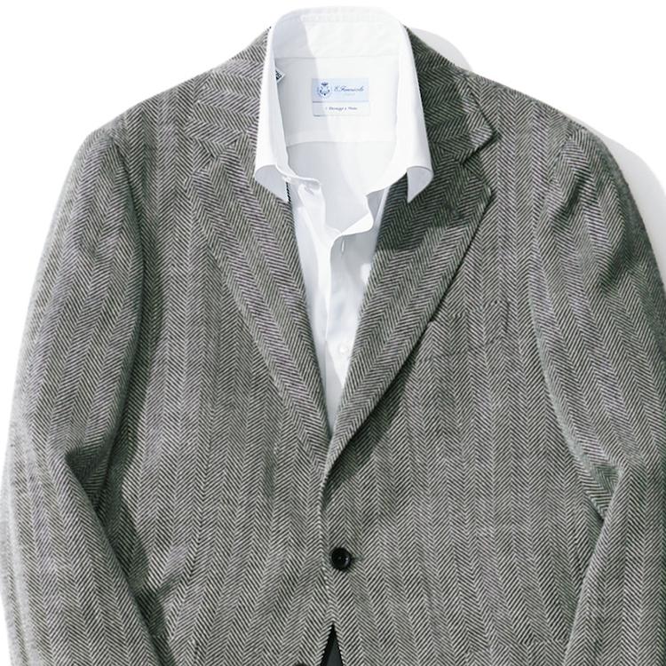 <p><strong>2位<br /> 白シャツ×ノータイは「おじさん化」に注意?【1分で出来るスーツのお洒落】</strong><br /> クールビズだからといってネクタイをはずした、白シャツとジャケットのスタイル。でもどこかおじさんっぽいなと感じたことはないだろうか? そんなときは、ジャケットにうっすらと柄が入っているものを選ぶと「おじさん化」を避けられる。こちらの写真も、もし無地のグレージャケットだったら、ただいつものビジネススタイルからネクタイをはずしただけに見えるだろう。だが、ほんのりヘリンボーン織り柄が入ることで、奥行きのある装いとなる。一捻りした洒脱なノータイスタイルで見せられるのだ。<br /> <small>(2020年6,7月号掲載)</small></p>