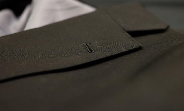 <p><strong>量産スーツのラペルはエッジも平面的</strong><br /> 安いスーツのラペルがこちら。カッターで切ったようにエッジが直線的で、のっぺりと平たく抑揚に欠ける。ロールがしっかり立体的でも、こういう細かな作りが高級感の差になってくる。</p>