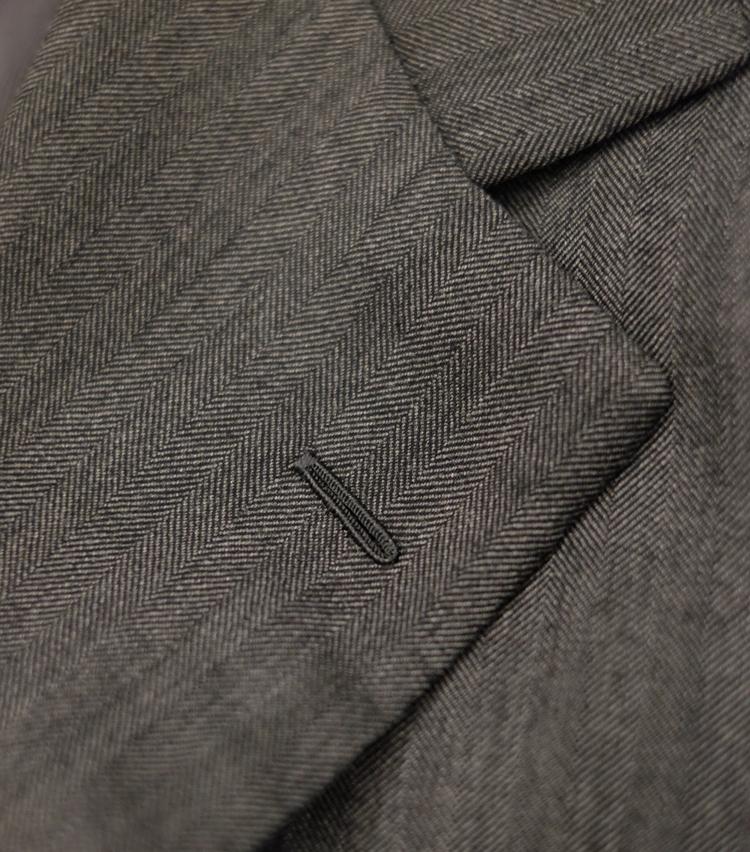 <p><strong>【Point 4】フラワーホールが美しい</strong><br /> スーツ好きな人ほど無意識に注目しているのがフラワーホール。職人の美意識が表れるディテールだ。いいフラワーホールは縫い目が細かく、立体的な山になっていて、ホールに歪みのないもの。写真はその好例だ。ちなみにこちらは手縫いによるもの。ビスポークなど最高級スーツは多くが手縫いでフラワーホールを仕上げている。</p>