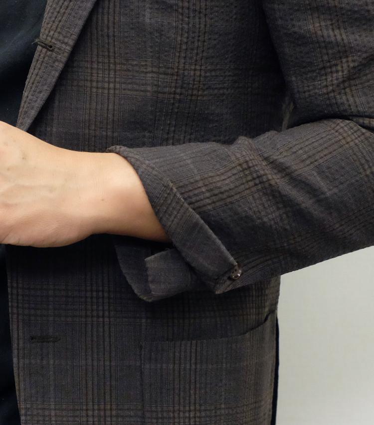 """<p><strong>【Technique 3】ジャケットの裾を""""0.5ロールアップ""""</strong><br /> 袖口のボタンが実際に開閉する「本開き」のジャケットで実践可能。ボタンをひとつ外し、袖先をペロリとめくるだけだが、あまりきちっとめくらず、袖の外側だけをめくるのがポイントだ。長袖シャツを着ているとシャツ袖が見えてヘンなので、半袖を着ているときに行うべし。</p>"""