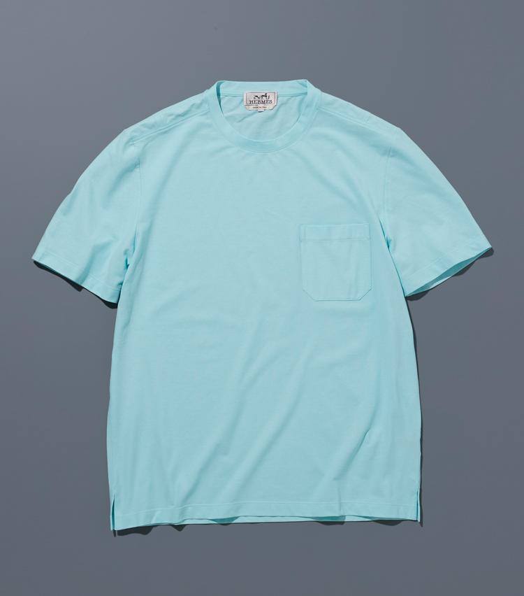 """<p><strong>エルメス</strong><br /> 毎シーズン、わずかな変化を加えながら展開されるロングセラーTシャツ。こちらはシーズナルカラーの一枚で、透き通るようなアクアブルーが、着る者にも見る者にも晴れやかな気分を与えてくれる。両肩にあしらわれた""""H""""のステッチがさりげないアクセントに。4万1000円(エルメスジャポン)</p>"""