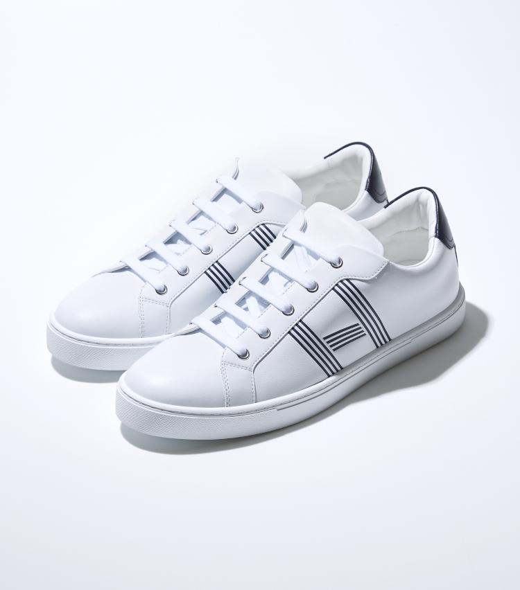 <p><strong>エルメス</strong><br /> 上質なホワイトカーフスキンによるテニスシューズ「アヴァンタージュ」は、エルメスのキーチャーム「カデナ」のラインにインスパイアされたストライプで表現されたサイドのHロゴが上品なアクセントに。余分な装飾を省いた、ミニマルなデザインがながら、白×紺による上品かつマリンテイストな配色が足元を軽快に彩ってくれる高級感溢れる一足に。インソールにカーフスキンを用いるなど、快適な履き心地が実現されている。10万3000円(エルメスジャポン)</p>