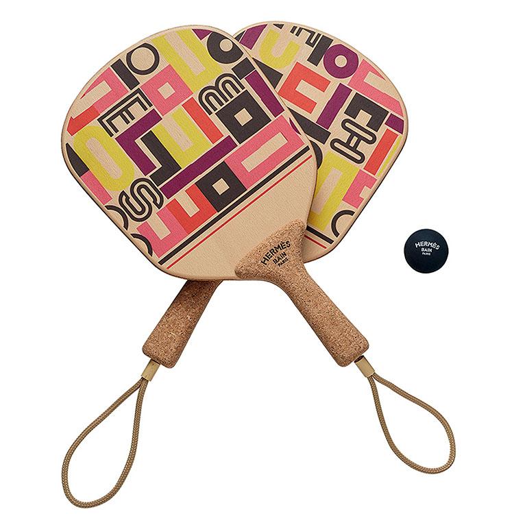 <p>ラバーボール付きで、ビーチサイドでのアクティビティを楽しめるビーチラケット。遊び心のあるアイテムで、旅先で盛り上がること間違いなしだ。ラケットの素材はブナとコルク。ラバーボール付き。こちらも「カレ・タカン」のデザインだ。10万2000円</p>