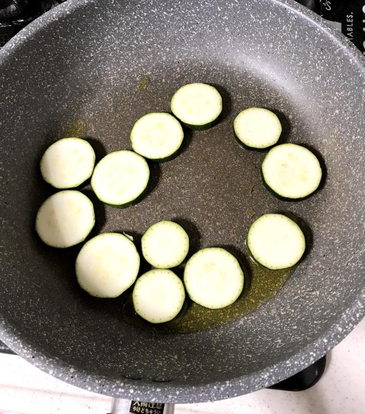 <p>2.フライパンにオリーブオイルを引き、ズッキーニを並べて、軽く塩をする。チーズの塩分があるので、塩は軽めに。</p>