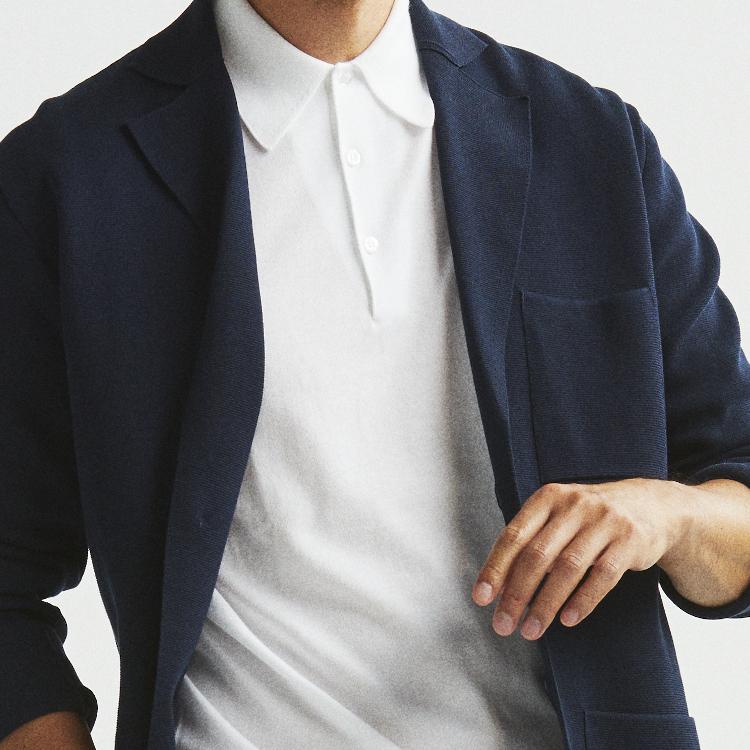 <p><strong>1位<br /> 一味違う「白ポロシャツ×紺ジャケット」の着こなしテク【1分で出来る胸元お洒落】</strong><br /> 白いポロシャツに紺ジャケットの組み合わせ。鉄板の組み合わせだが、素材感にも気を配るとまた違った表情の着こなしになる。例えばこの写真はニットポロにニットジャケットを重ねたもの。ニット素材の掛け合わせによるハーモニーが、洒脱を演出してくれるのだ。<br /> <small>(2020年8月号掲載)</small></p>