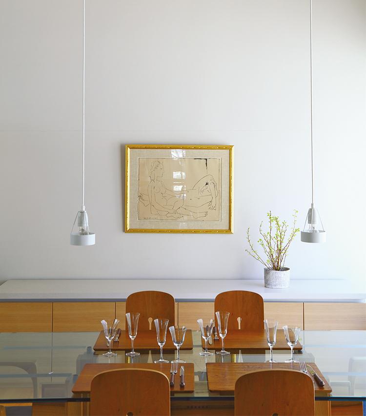 <p>アートは自宅のコレクションから選んで飾り、ゲストや空間に合わせて替えている。リ・ウーハンやブラック、篠田桃紅らが好み。ダイニングはイタリアの家具メーカーBerniniのガラスのテーブルと椅子、キッチンと同じVarennaの収納家具でナチュラルモダンにコーディネート。</p>