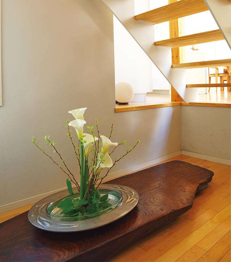 <p>普段は周辺に自生する草花、ゲストを迎える日は花屋から取り寄せた花を、自身で生けて楽しんでいる。花器はいぶし銀のオーバル皿、漆の花台は大阪のレストラン「カハラ」のオーナーシェフ・森義文氏より贈られた自作の品。</p>