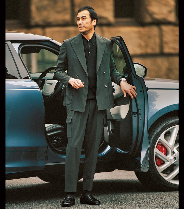 """<p><strong>「ボックスシルエットも気分」(平澤)<br /> 「現場で売れそう!と話題に」(小曽根)</strong><br /> 3月号で""""ネロ エ ヴェルデ""""こそ最旬の配色と提案して以来、旬の緑のスーツ×黒の合わせを頻繁に推してきた本誌。「中でもこちらのゆったりめのダブルにカーゴパンツを合わせたデザインワークスのセットアップは、撮影現場で売れそうと話していました。ここに黒Tを合わせても良さそう」(平澤)。<figcaption>(6・7月合併号<a href="""