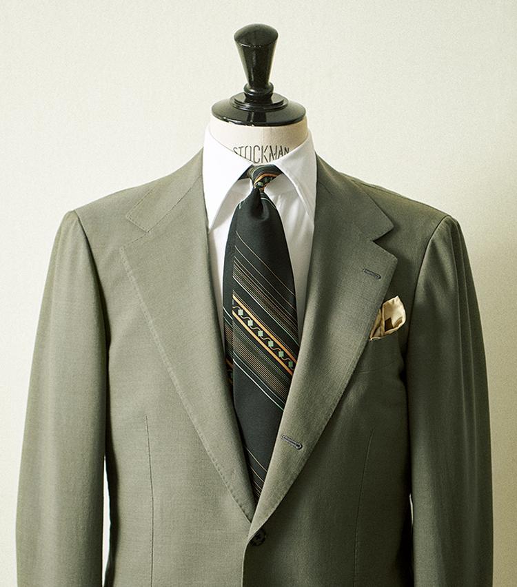 <p><strong>「パネルタイも雰囲気◎」(金森)</strong><br /> 「このリングヂャケットのスーツは緑とグレーの間の色味が本当に綺麗。黒ベースのパネルタイも旬気分を高めています」(金森)<figcaption>(5月号<a href=