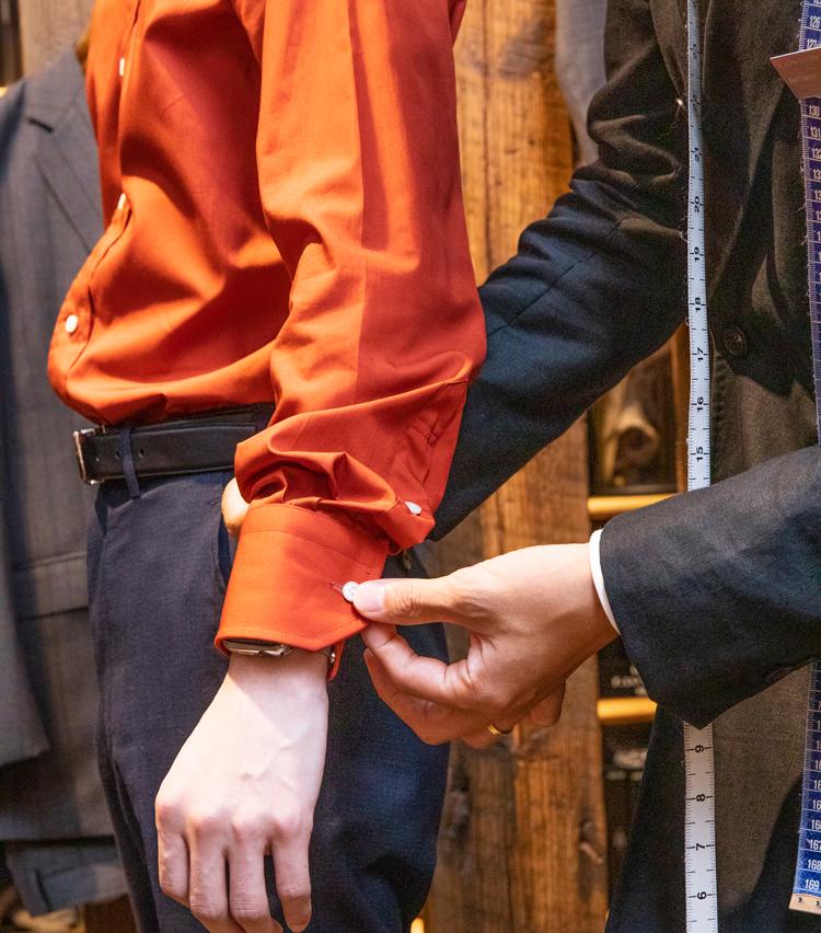 <p><strong>袖は、さらに細くすべし</strong><br /> 続いて袖丈の補整。やや長いので少し短くすることに。それに加えて、袖の幅についても補整が必要とのこと。「袖の幅が緩いように見えます。スリム袖という細くできる仕様があるので、それを追加しておきますね」</p>