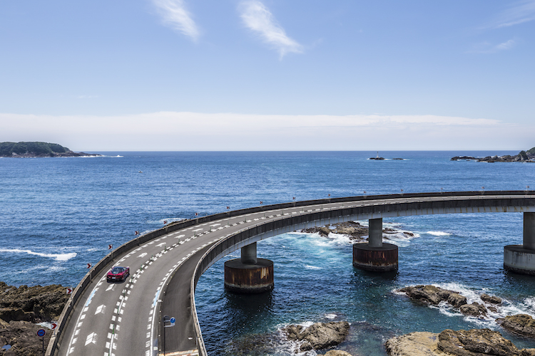 <p>大島へと至るループ橋。真っ青な海とマクラーレンGTの赤とのハイライトが美しい。</p>