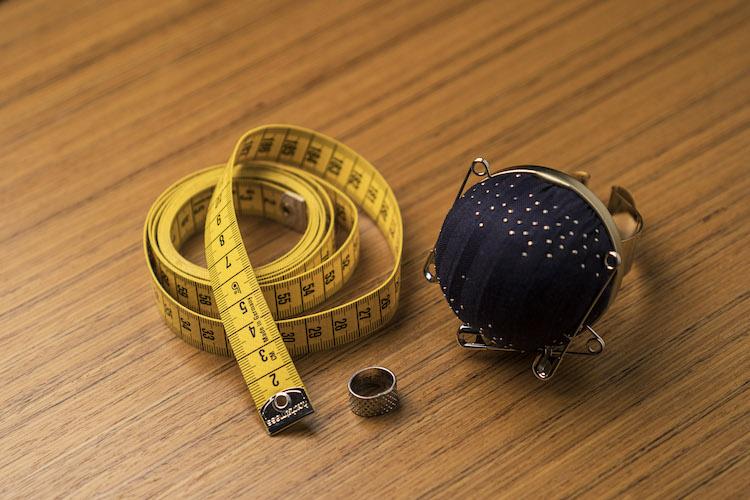 <p>【お仕事道具】左からメジャー、指貫(ゆびぬき)、針山。メジャーは2mとあまりない長めのものを使用。指貫は指の形にフィットするように、自分で楕円形に加工してある。針山はドーメルの記念品。バングル風に腕に着けるデザインが「かっこよくて気に入っています」とのこと。</p>
