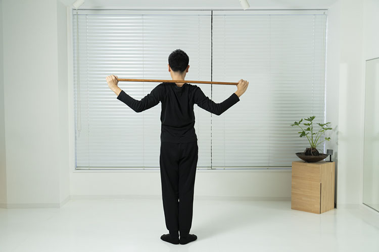 <p>そのまま肘を曲げて、頭の後ろに棒を下げる。これを12回繰り返す。</p>