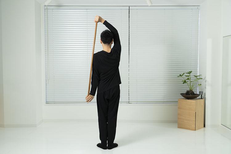 <p>右手を上へ、左手を下にしながら、棒を体の左側へ回す。</p>
