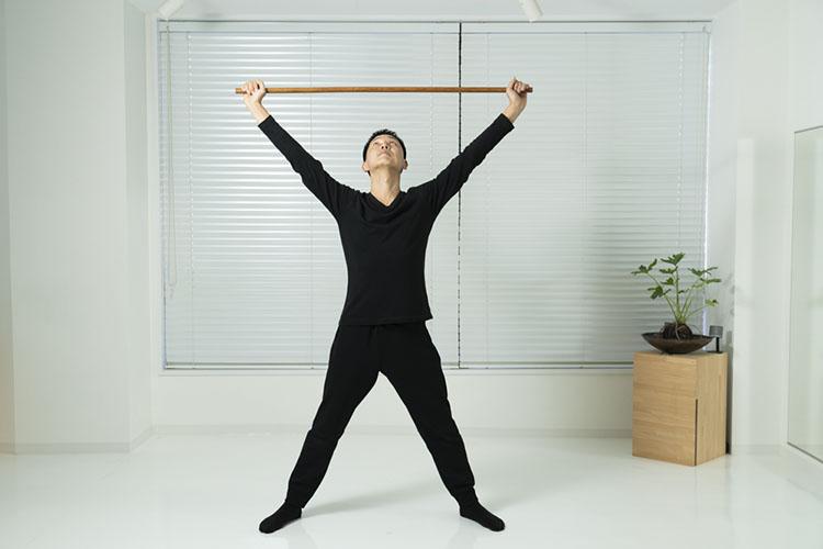 <p>肩幅よりやや広く脚を開いて立ち、棒の両端を持って、頭の上にあげる。</p>