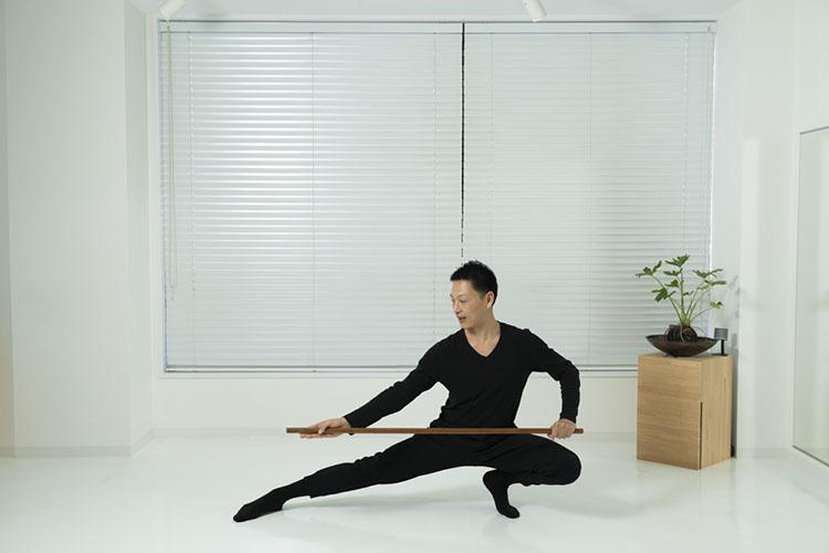 <p>肩幅よりやや広く脚を広げて立ち、棒を縦に持ってそのまま腰を落とす。重心を左に移動させ、右足を伸ばし、床と平行になるように棒を持つ。</p>