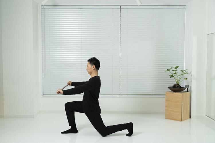 <p>肩幅の広さで棒を持ち、しゃがみ、左脚を後ろへ下げて膝をつき、右脚は前に出す。両手を伸ばし、棒は胸の位置に。</p>