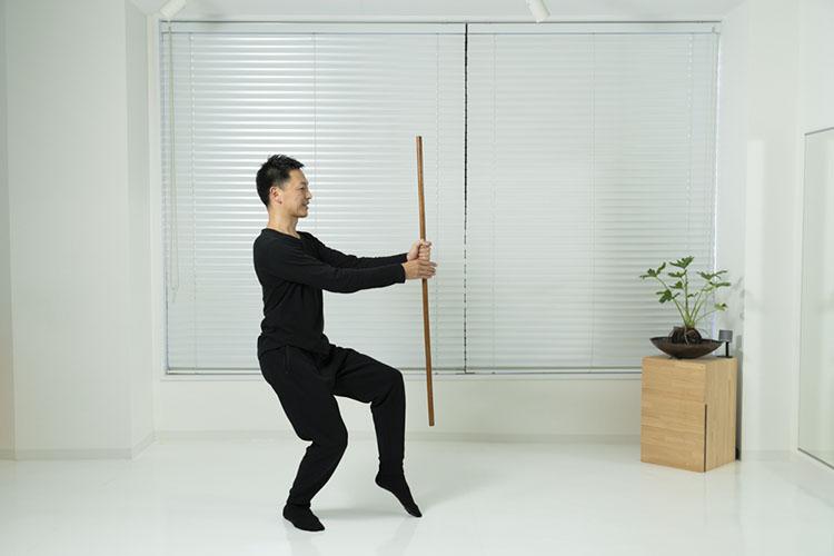 <p>棒を縦に持ち、腰を少し落として、右脚を前に出して爪先立ち、左脚は膝を少し曲げてかかとをつける。</p>