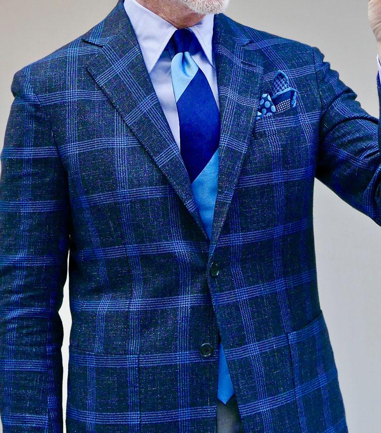 <p><strong>3.シルクタイで魅せる光沢エレガンス</strong></p> <p>程よいネップ感がある風合い豊かなネイビー地に、ブルーのクラスターストライプによる格子が走った爽やかな素材感のジャケット。無地シャツは上着の素材感に合わせて織り柄モノを選ぶも、タイは光沢シルクでエグゼクティブらしい品格を加える。ネイビーも色のトーンや素材感を変えれば着こなしの幅もこんなに広がる。シルクチーフを挿せば夜のムードが高まる。</P></p>
