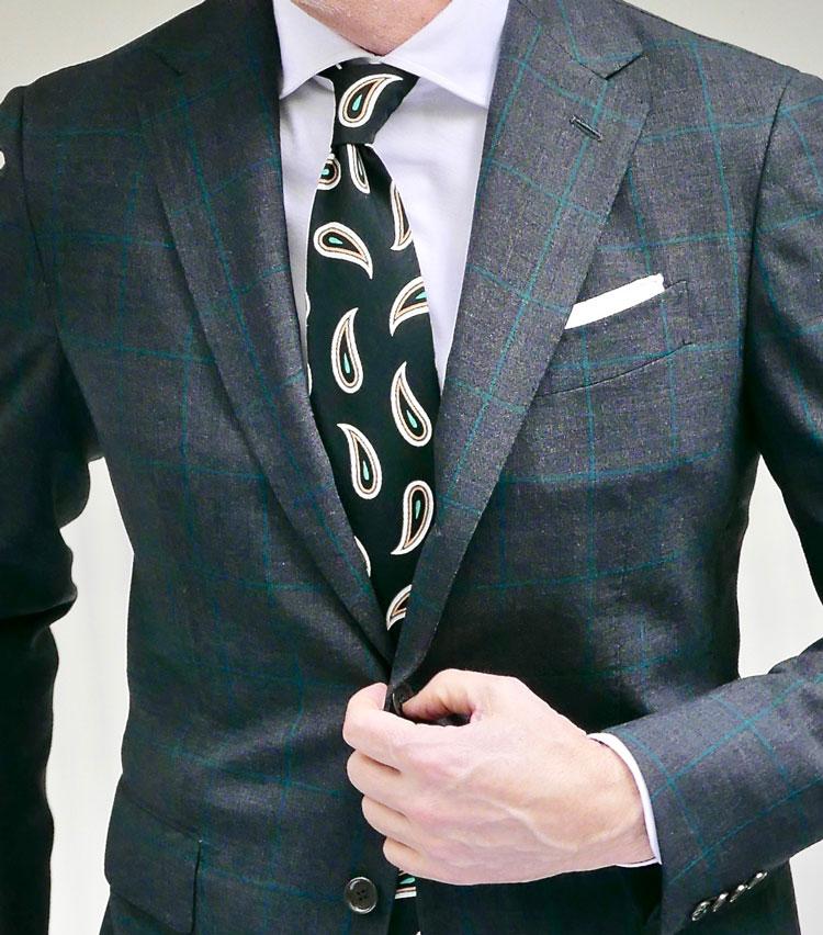 <p><strong>1. 黒タイの引き締め効果を狙う</strong></p> <p>遠目無地に見えるグリーンのペーンが入ったグレースーツ。ソリッドなブロードの白シャツに、黒ベースのビッグペイズリータイで時には大胆な男を演出する。スーツに走るペーンのグリーンを、ペイズリータイのグリーンで拾うあたりに、スーツを着慣れた男のさりげない上級者テクを垣間見た。</p>