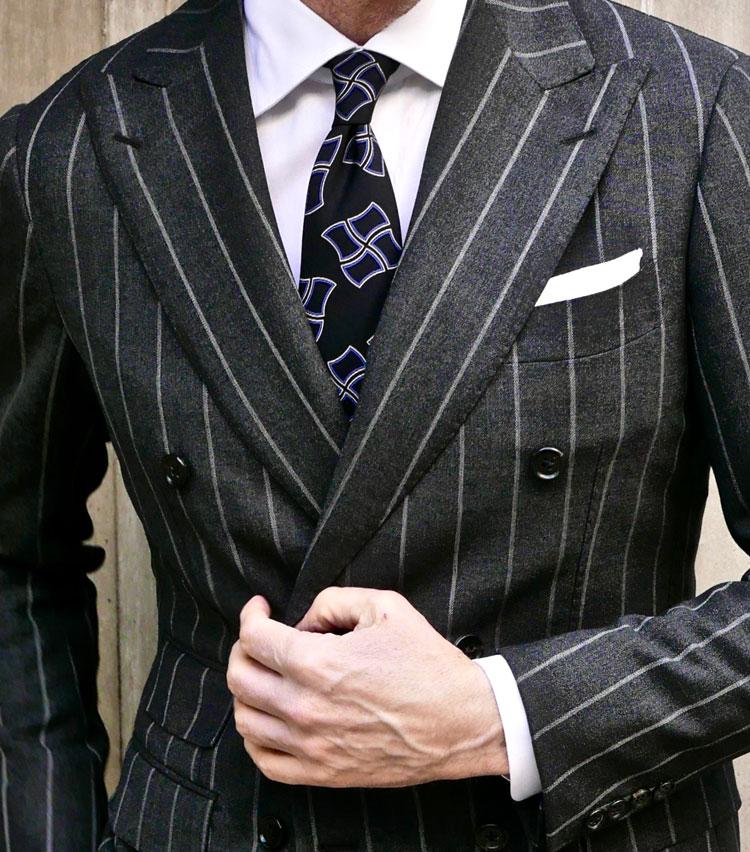 <p><strong>3.王道ストライプには幾何学柄タイで新鮮味を</strong></p> <p>ストライプ柄のスーツはよくあるが、ダブルスーツほど上品にストライプ柄を着こなせるようなスーツは他にない。クリーンな白シャツに、黒ベースに薄っすらパープルがかった幾何学柄のタイをコーディネート。チーフは白をTVフォールドで控えめを意識する。シャープで精悍なイメージを演出してくれるに違いない。</P></p>
