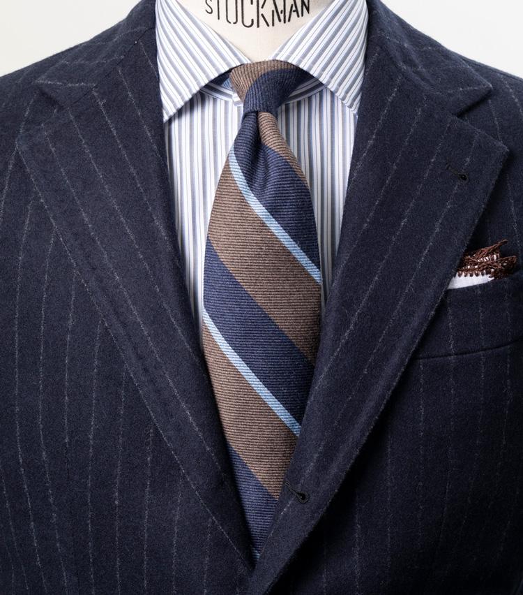 <p><strong>ビジネスの王道に控えめな洒落感をプラス</strong></p> <p>ネイビーのチョークストライプスーツによるドレスウェア王道の着こなし。タイは3配色のストライプで、シルクタイのようなパキっとした鮮やかな色のものでなく、スモーキーな色みのもので合わせている。より控えめで落ち着いた洒落感が打ち出されている。<br /> <small>スーツ35万円/アルフォンソ シリカ、シャツ3万6000円/ルイジ ボレッリ、タイ1万3000円/ブリューワー、チーフ7000円/ムンガイ(伊勢丹新宿店)</small></p> <p><a class=