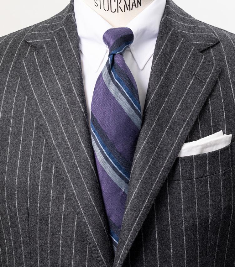 <p><strong>大人の色気をあくまで品良く薫らせる</strong></p> <p>グレーストライプのスーツに白シャツと、英国のバンカーのようなきっちりとした上品な着こなし。そこにネクタイでパープルを加えることで、どこか大人の色気が感じられる。タイの生地は麻と綿を主に用いているので、シルク100%のものより発色が抑えられ、パープルの色合いも落ち着いてみせられるのだ。<br /> <small>スーツ15万6000円/デ ペトリロ、シャツ2万6300円/エリコ フォルミコラ、タイ1万6300円/ブリューワー、チーフ2700円/シップス(シップス 銀座店)</small></p> <p><a class=
