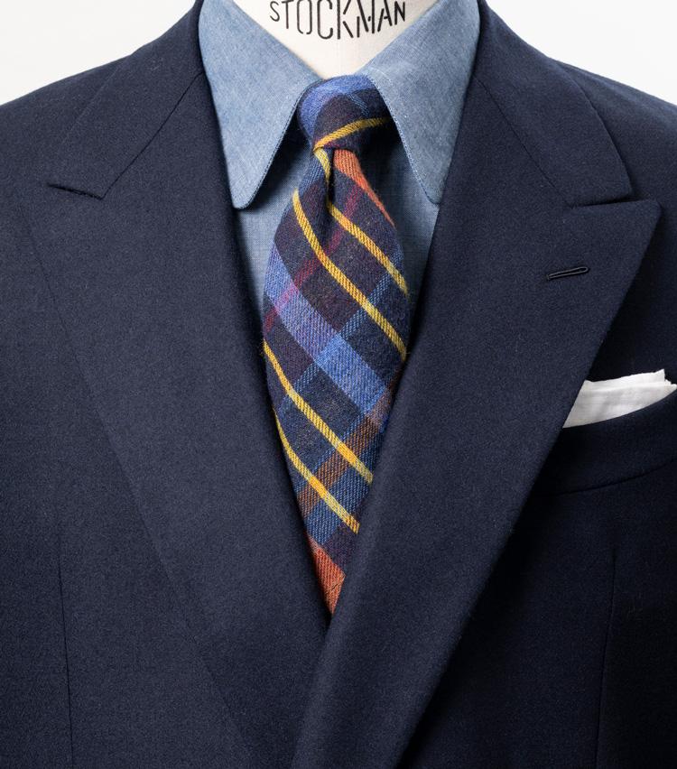 <p><strong>トラッドなチェック柄をモダンな配色で愉しむ</strong></p> <p>オーセンティックなチェック柄だが、フレンチブルーにオレンジやイエローを組み合わせた、モダンな配色のネクタイを主役に据えた着こなし。一見難しそうな色使いも、タイの色柄を拾ってブルー系でまとめればしっくりと着こなしに馴染ませることができる。<br /> <small>スーツ16万3000円/カルーゾ、シャツ2万2700円/ギ ローバー、タイ1万6300円/ブリューワー、チーフ2700円/シップス(シップス 銀座店)</small></p> <p><a class=