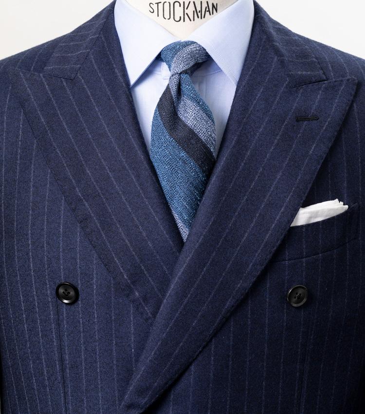 <p><strong>タイの生地感で洒落心を表現</strong></p> <p>ネイビーのストライプスーツ、サックスブルーのシャツ、ブルーストライプのネクタイと、コンサバな組み合わせだが、注目すべきはネクタイの生地感。ネップ感の強い生地が、ベーシックな装いのアクセントになっている。コンサバベースだが、一歩進んだ着こなしが表現されている。<br /> <small>スーツ12万7000円/ヴァルディターロ ペル シップス、シャツ2万1800円/サウスウィック、タイ1万6300円/ブリューワー、チーフ2700円/シップス(シップス 銀座店)</small></p> <p><a class=