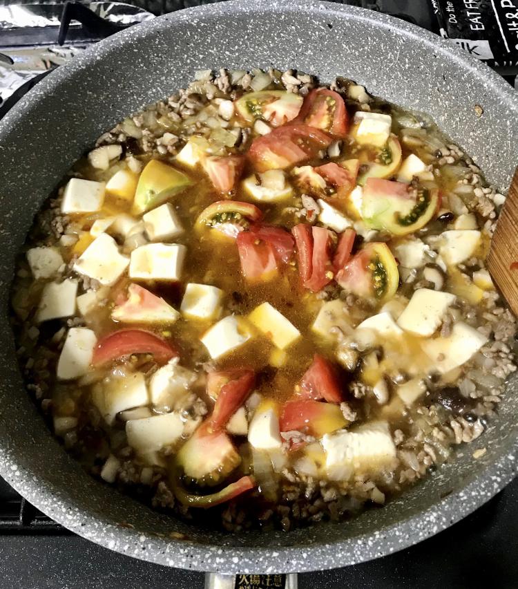 <p>7.3分ほど煮たら、トマトと長ネギの残りを投入、トマトが柔らかくなってきたら、一旦火を止め、水溶き片栗粉を回し入れ、全体を混ぜたら再度火をつけ、粉っぽさを飛ばすように強火で焼き付け、仕上げにごま油少々を回し入れたら完成です。</p>