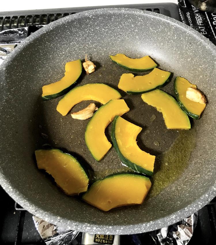 <p>4.ニンニクが色付いたらかぼちゃを入れ、中火で焼き付ける。あまり触らず、じっくりと焼き目を付けるのがポイント。</p>