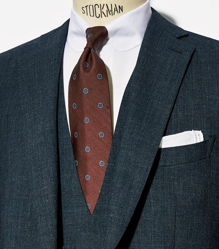 <p><strong>これまでにも提案してきた1.5柄の合わせ技</strong><br /> 織柄のあるクラシックなグレーのスリーピースに渋色ブラウンの小紋タイを。クールで落ち着いた表情。</p>