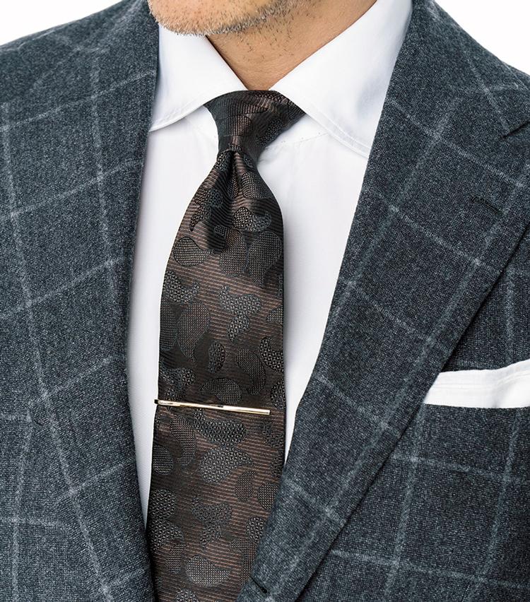 <p><strong>これまでにも提案してきた1.5柄の合わせ技</strong><br /> 起毛したフランネル系のスーツに、ブラウンベースの光沢シルクタイがシャープさを生む。</p>