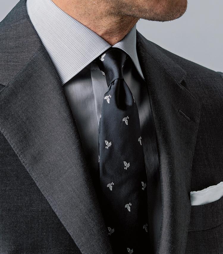 <p><strong>これまでにも提案してきた1.5柄の合わせ技</strong><br /> ソリッドな光沢スーツとマイクロチェックシャツに、シルクサテンのタイを挿す。グレーのトーンがひときわクールだ。</p>