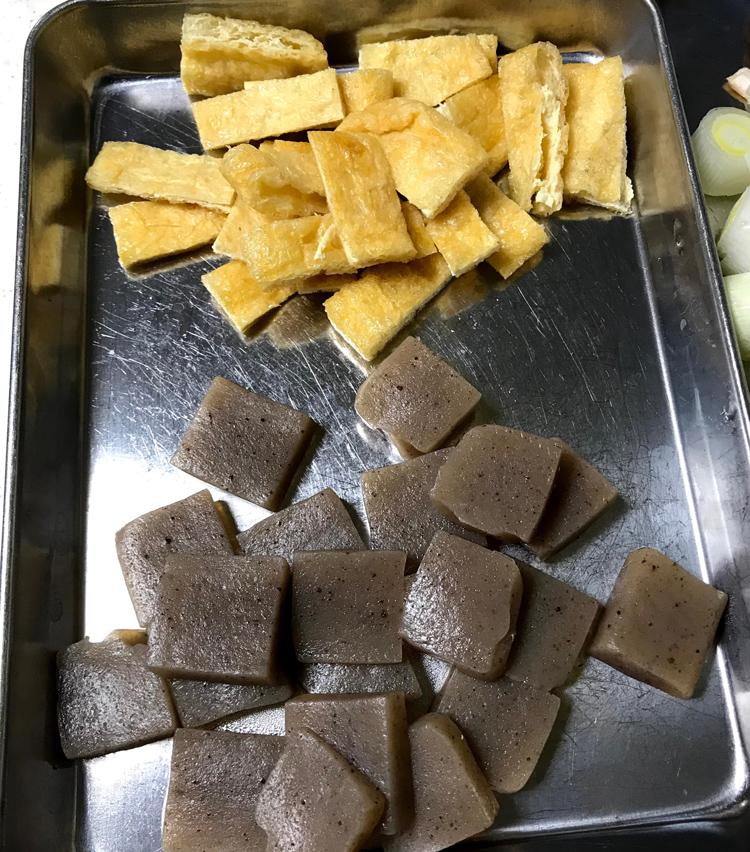 <p>2.材料を切る<br /> 大根は皮を剥き、いちょう切りに。人参は皮を剥き、輪切りに。玉ねぎは5ミリの薄切りに。ごぼうは斜め薄切りにし、水にさらす。長ネギは1cmの輪切りと薬味用に小口切りに。椎茸は軸を取り、薄切りに。油揚げは1cm巾に切る。こんにゃくは5ミリ厚の短冊切りにし、塩揉みし、3分ほど茹でる。</p>