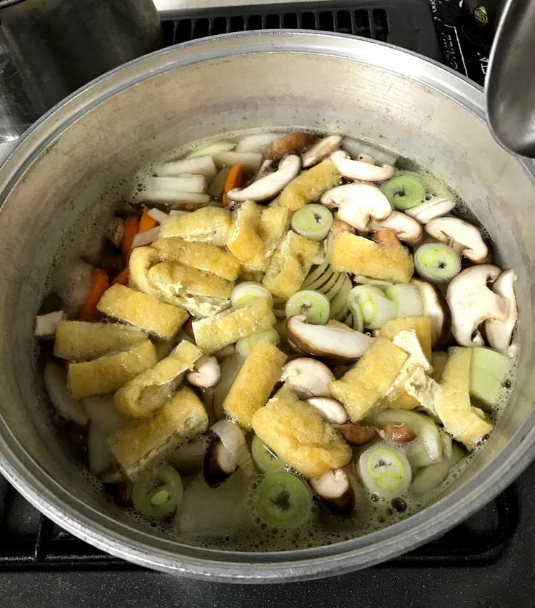 <p>5.煮たったら灰汁をとり、だしの素小さじ2、酒大さじ2を入れ、その他の具材も入れる。</p>